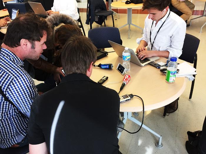 Reportrar lyssnar på Clintons möte inne i skolan via mobiltelefon.