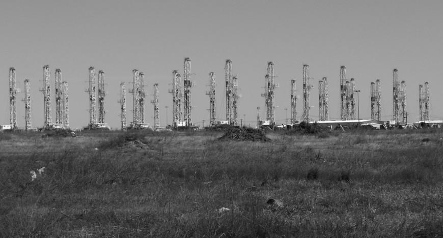 Oanvända oljeborrtorn står i parad på slätten.