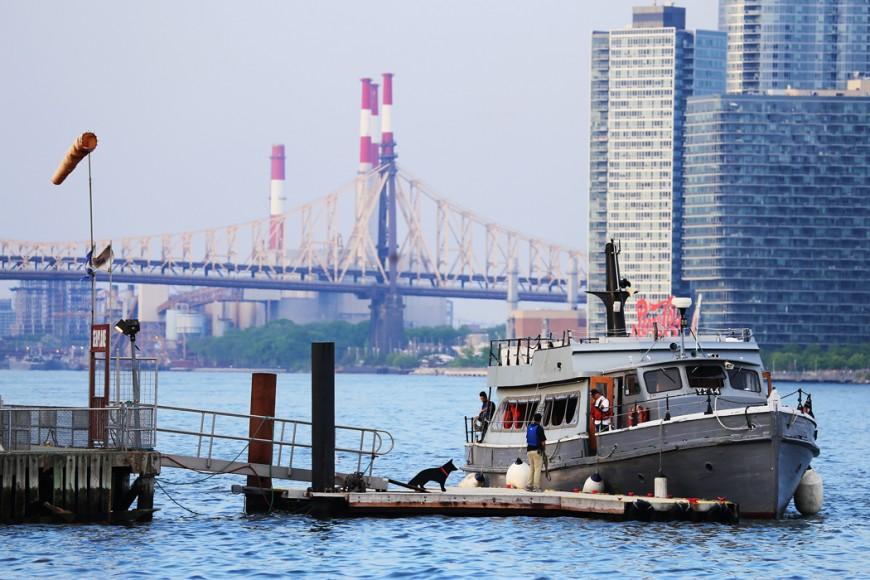 Vad som troligen är en charterbåt lägger till vid en brygga vid 20:e gatan.