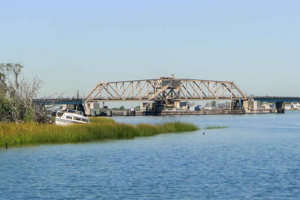 En övergiven fritidsbåt ligger i strandkanten nära en bro i Jamaica Bay.