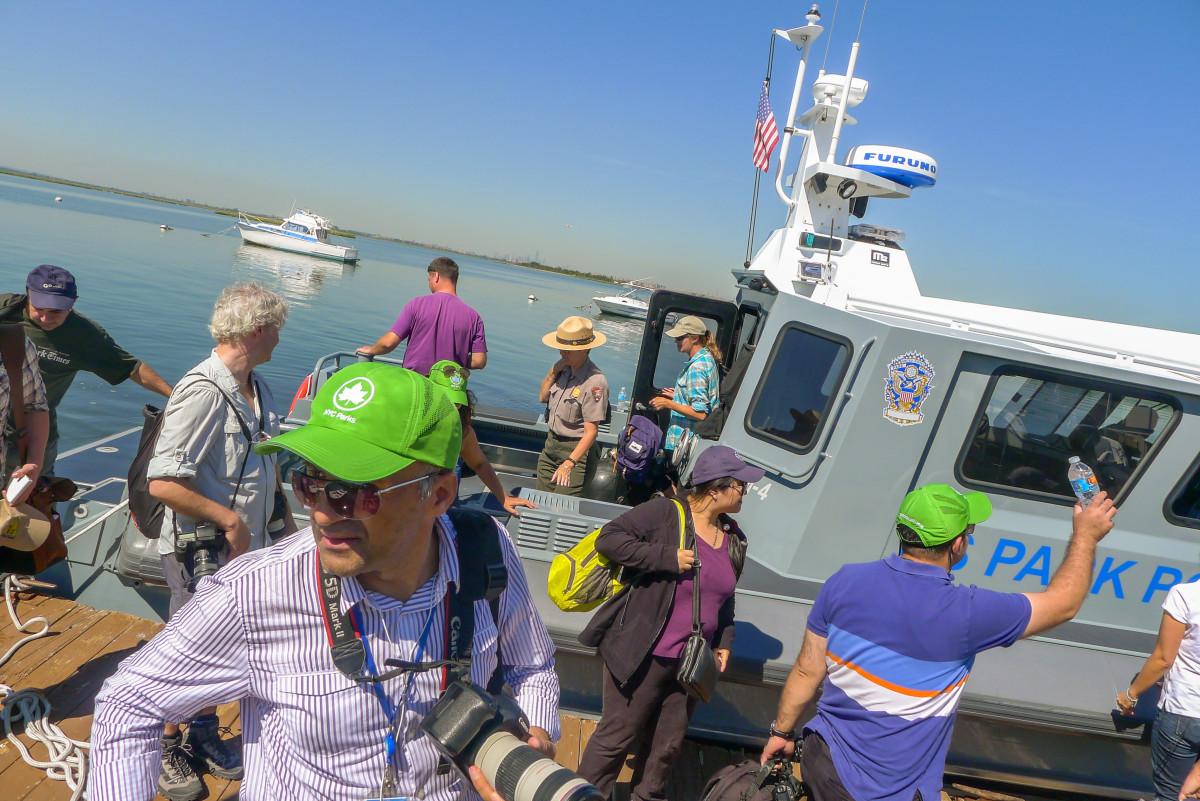 Journalister debarkerar polisbåten efter en fin tur i varmt väder runt Jamaica Bay.