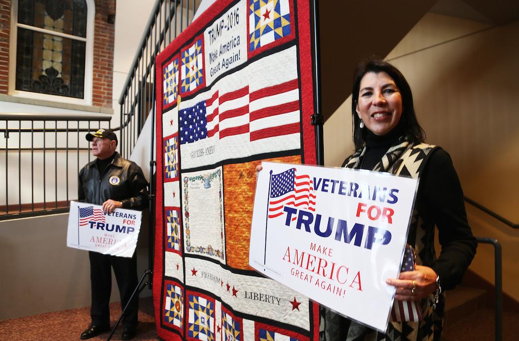 """Christine och John Heimburger från Houston, Texas, väntar på Donald Trump. Mellan sig har de en 2x2 meter stor gobeläng som Christine ägnat en månad åt att sy. Där finns Trumps slagord """"Make America great again"""" och hyllningar till USA:s väpnade styrkor. John är flygveteran från Vietnamkriget. – Vi åkte upp från Houston enbart för detta, säger han."""