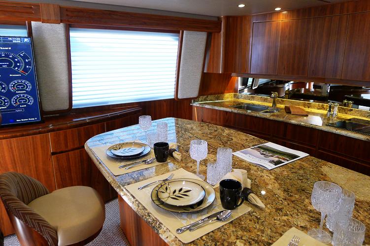 Middagsbordet i Vikings 70-fotare. Bakom bänken till höger finns köket. TV:n till vänster hissas upp och ned ur en lucka i träpanelen och kan visa digitala instrument för båtens två motorer, elsystem, vatten- och bränsletankar och annat.