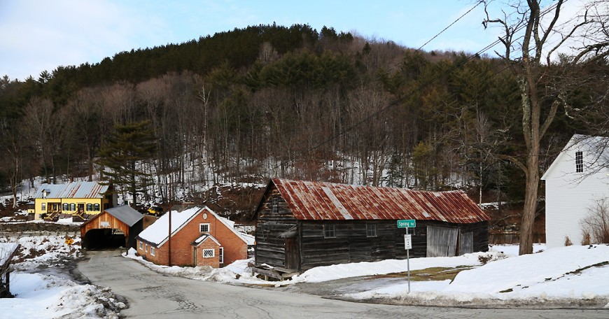 En övertäckt bro korsar floden i Tunbridge, Vermont, där en mer eller mindre övergiven kvar finns belägen nere vid strandbanken.