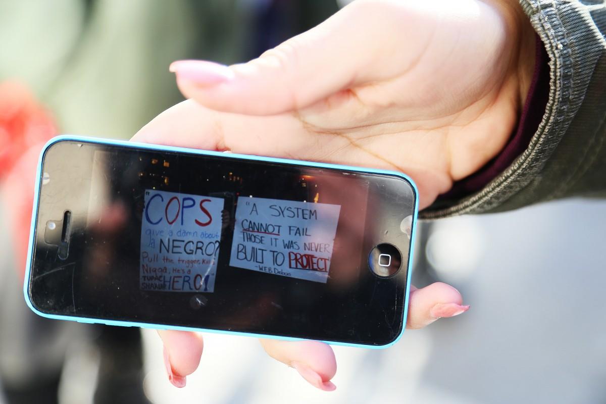 Kasey Felix, student från Harlem, visar foton i sin mobil av plakat som användes vid Ferguson-protesterna i november.