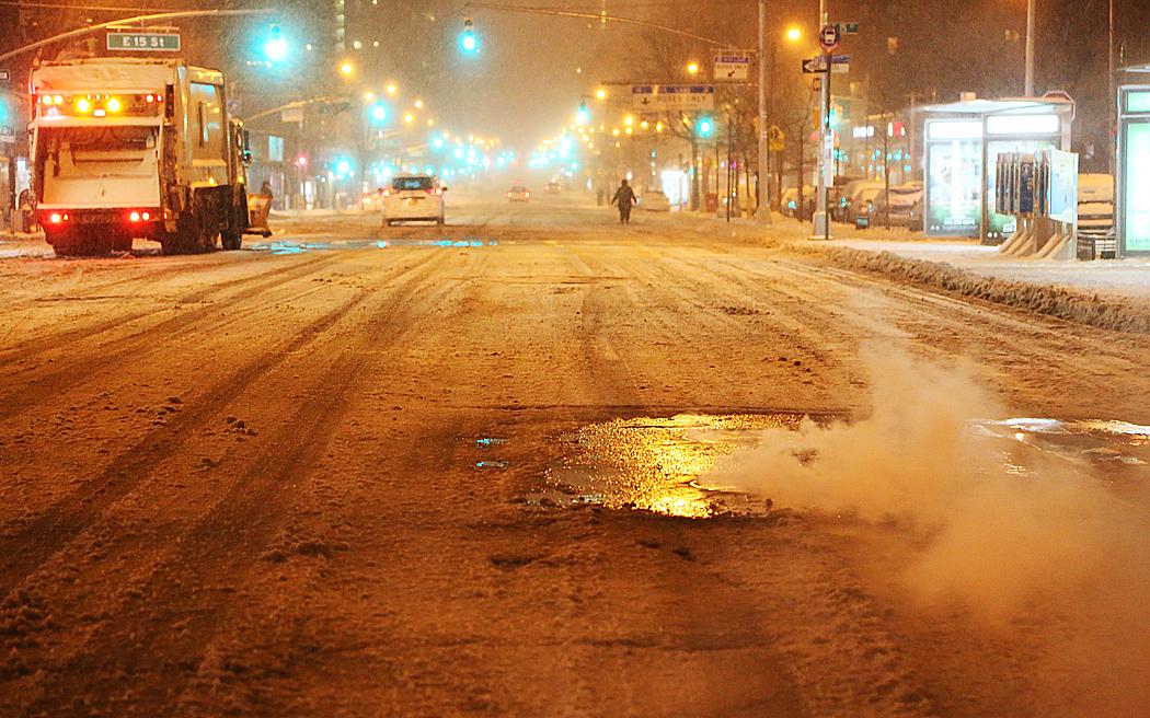 Ånga pyser upp från ett brunnslock längs Första avenyn, där en plogförsedd sopbil försöker hålla snön borta.