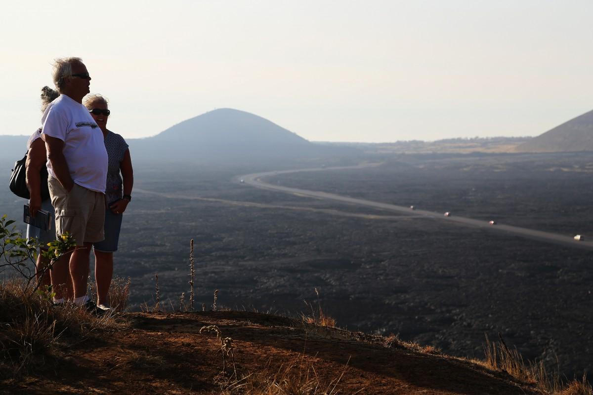 Turister betraktar de vidsträckta lavafälten nedanför Mauna Kea, som kommit från närbelägna vulkanen Mauna Loa.