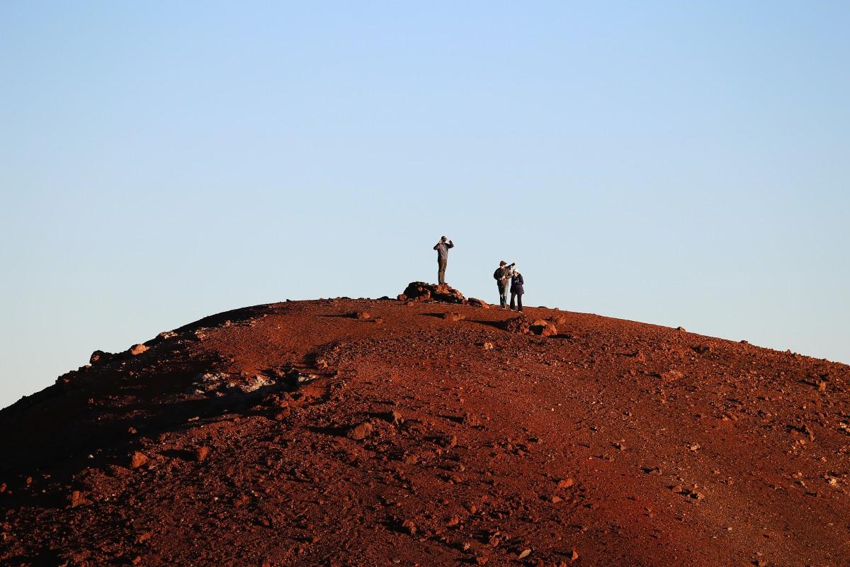 Några hikers har bestigit den högsta toppen en bit bort.