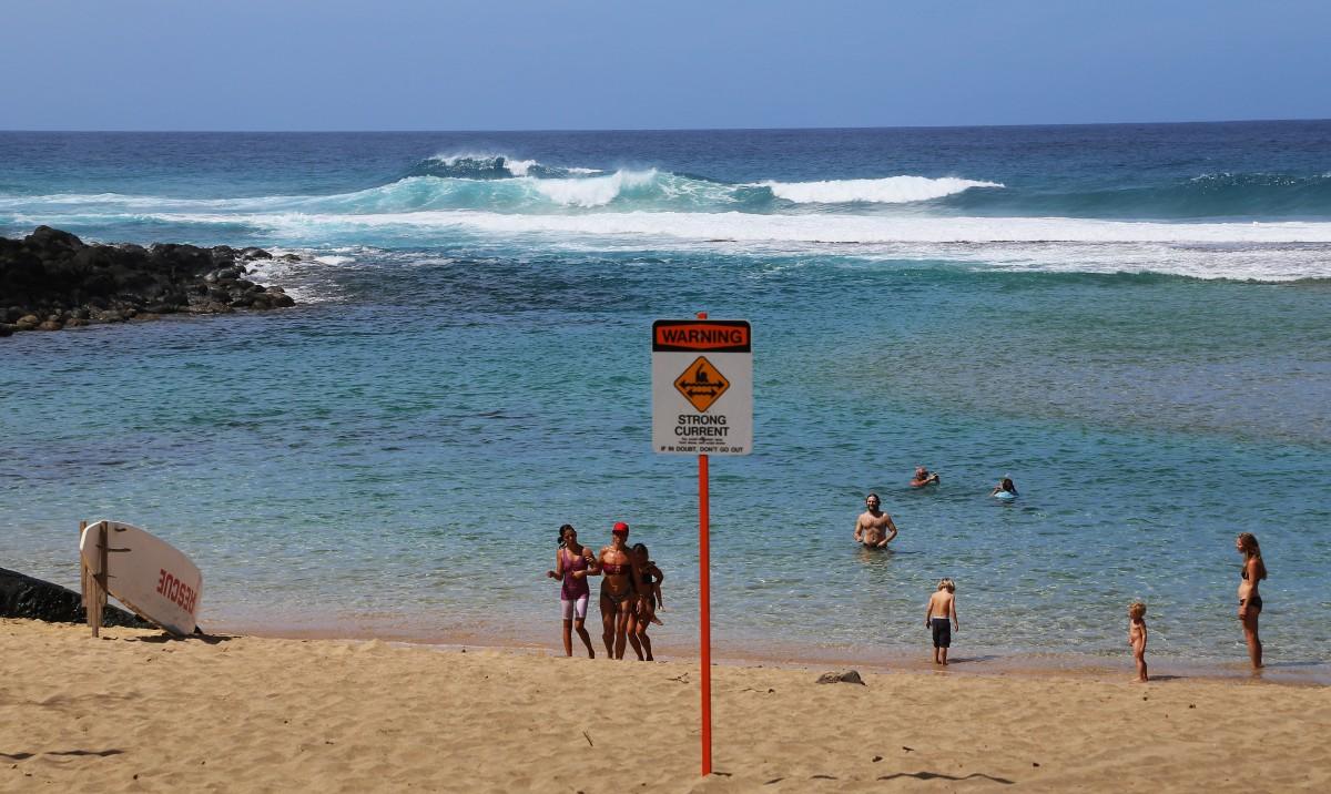 Skylten varnar för strömmar i vattnet.