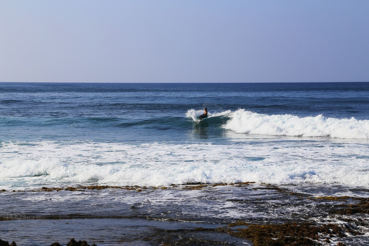 En surfare vid en enslig strand nära Oahus västra spets.