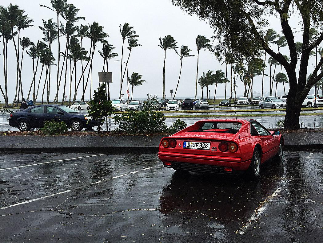 En Ferrari står övergiven på en regnig parkering i Hilo. Är det månne Magnums bil? frågar man sig, tills man ser att den bisarrt nog har tyska plåtar.