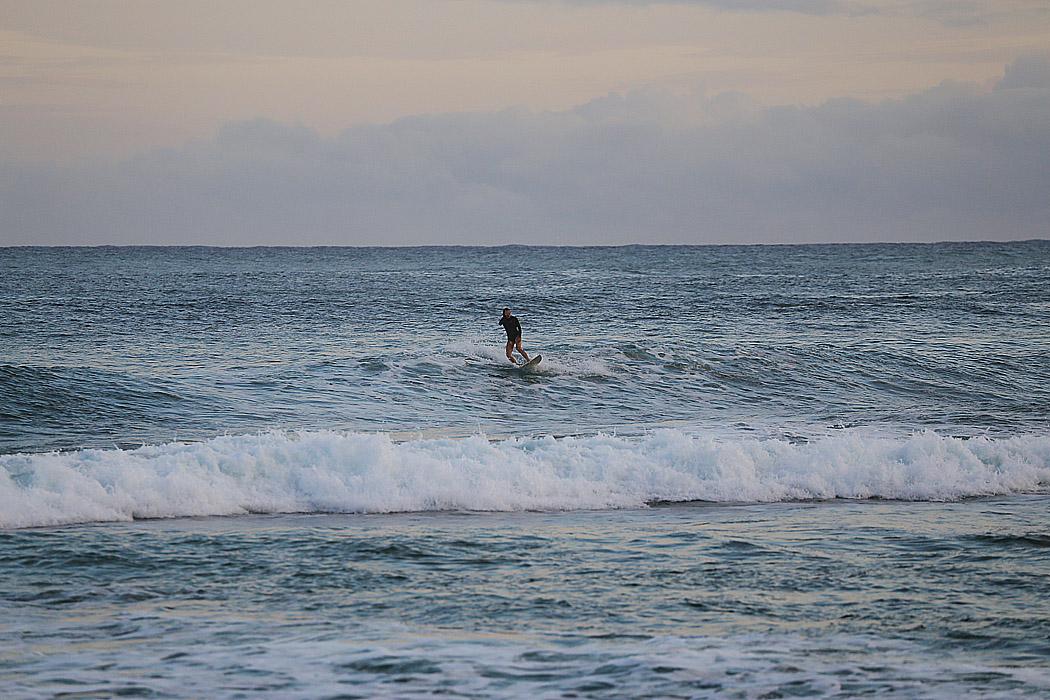 En ensam surfergirl hittar en bra våg.