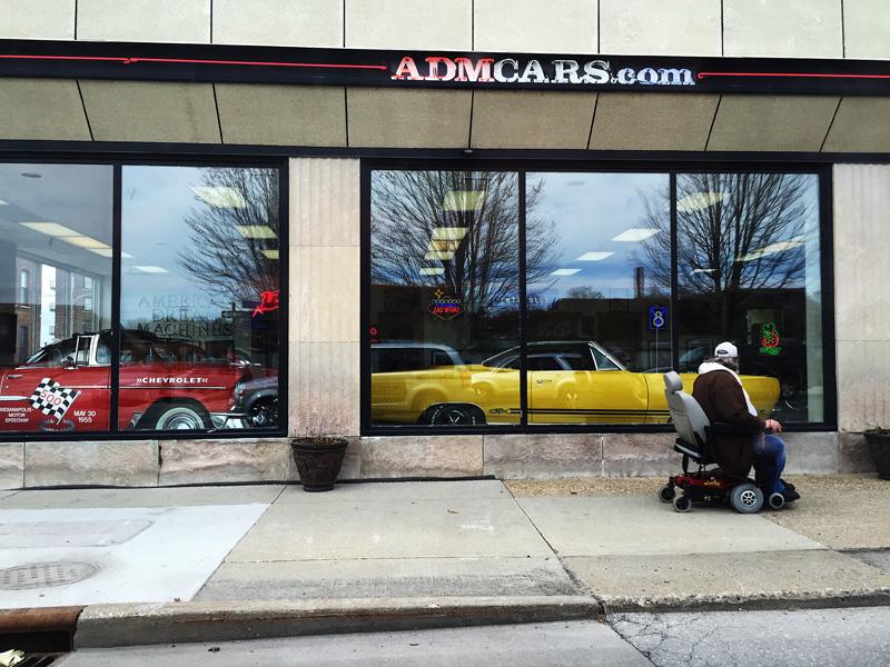 En rullstolsburen herre tittar drömmande in hos bilhandeln och dess gamla amerikanska veteran-vrålåk. Fotot taget från taxin på väg in från flygplatsen.