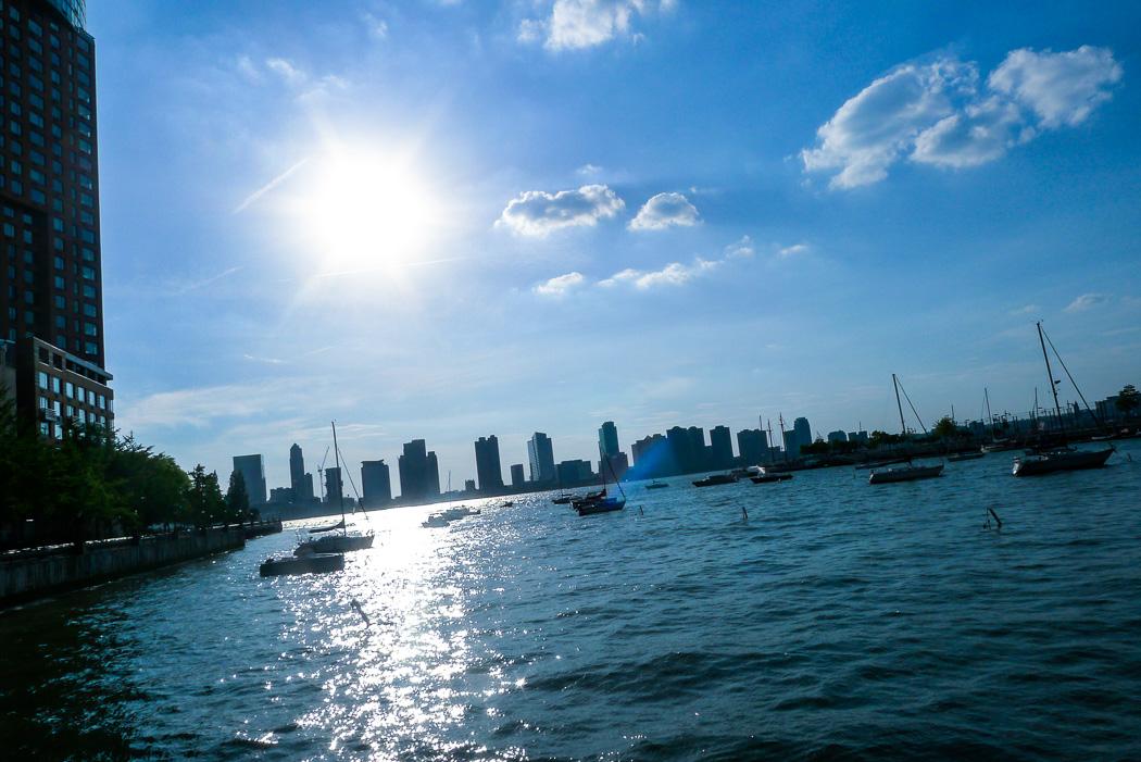 Småbåtshamnen vid södra inloppet till Hudson River, med New Jersey i motljus på andra sidan.