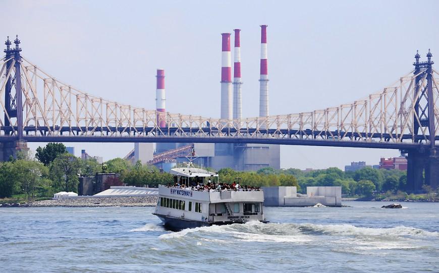 En turbåt stävar norrut mot Queensboro Bridge.