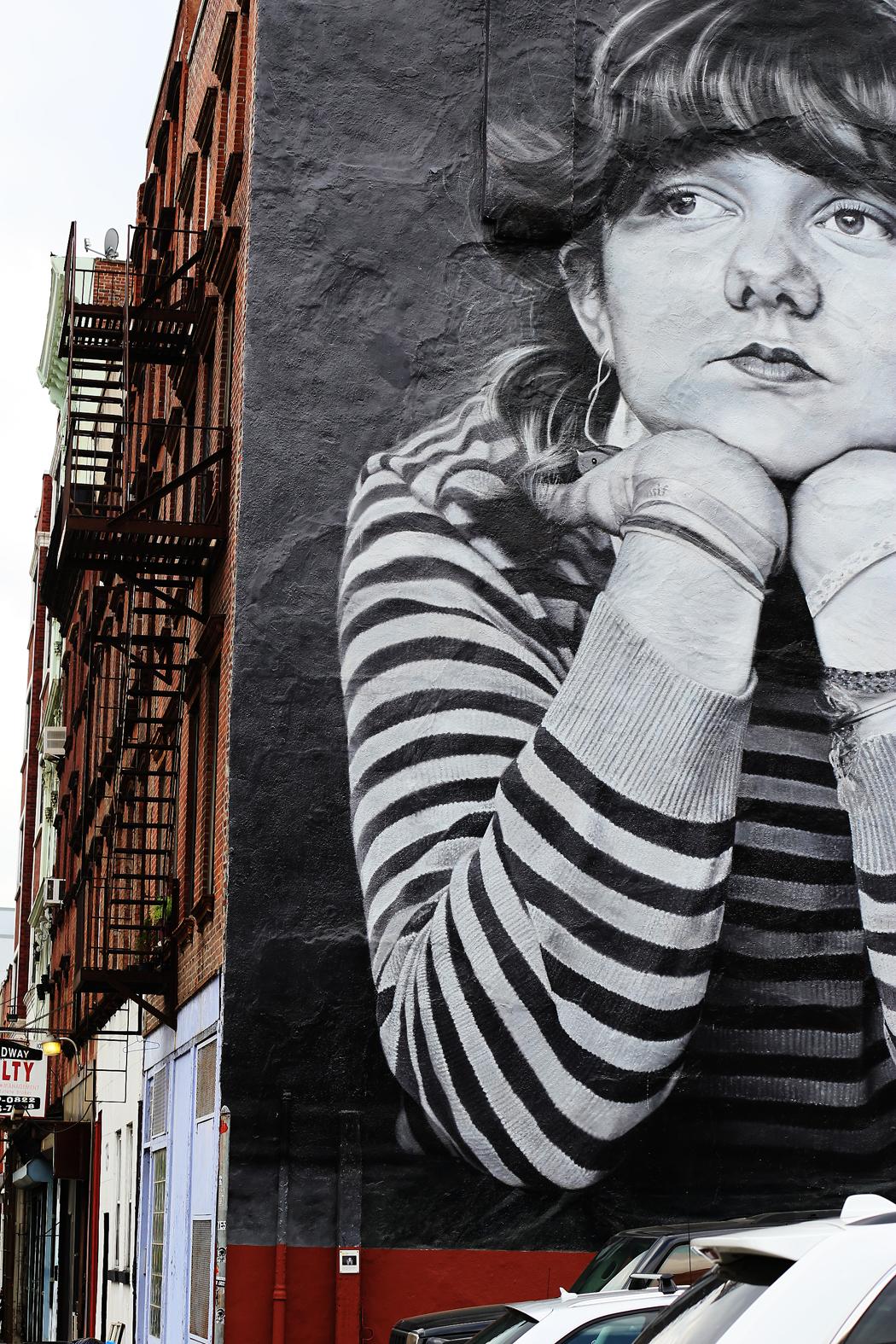 En muralmålning i form av en ung tjej. Man undrar över bakgrunden - någon som vet?