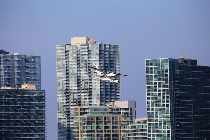 Ett pontonplan går in för landning på East River. I bakgrunden syns bostadshusen vid Long Island City/Hunter't Point, Queens.