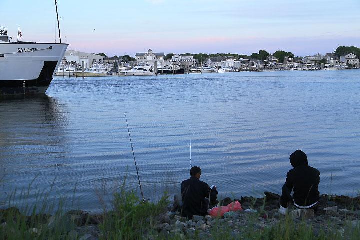 Två snubbar fiskar i hamnen i Hyannis, Cape Cod.