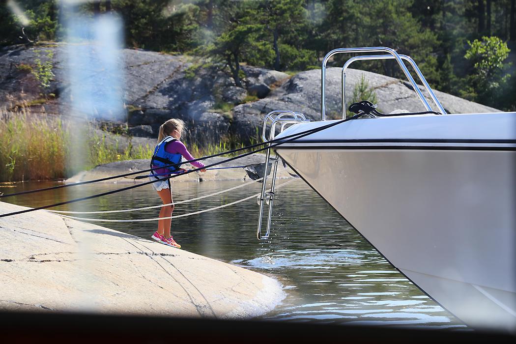 Ett barn leker med håv vid Ostholmen.