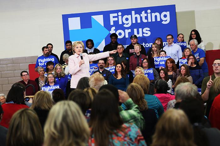 Hillary Clinton försöker övertyga väljarna om att hon är av rätta virket. En Clinton-supporter viftar med plakat utanför den samlingssal där den förra utrikesministern håller tal på fredagen. Foto: Erik Bergin