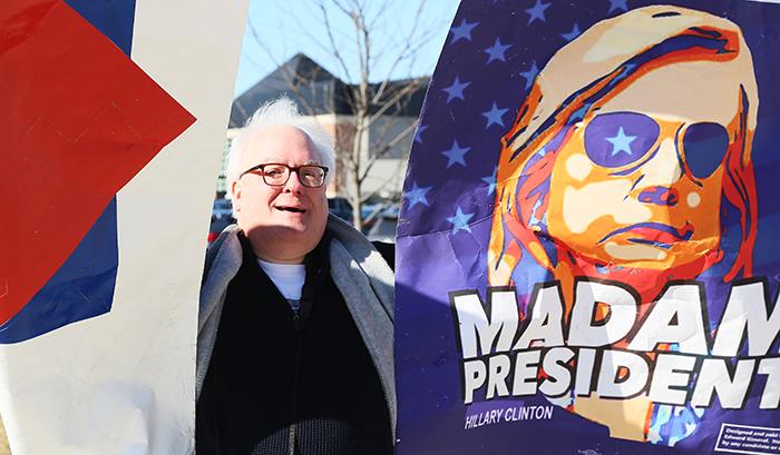 En Clinton-supporter viftar med plakat utanför den samlingssal där den förra utrikesministern håller tal på fredagen. Foto: Erik Bergin