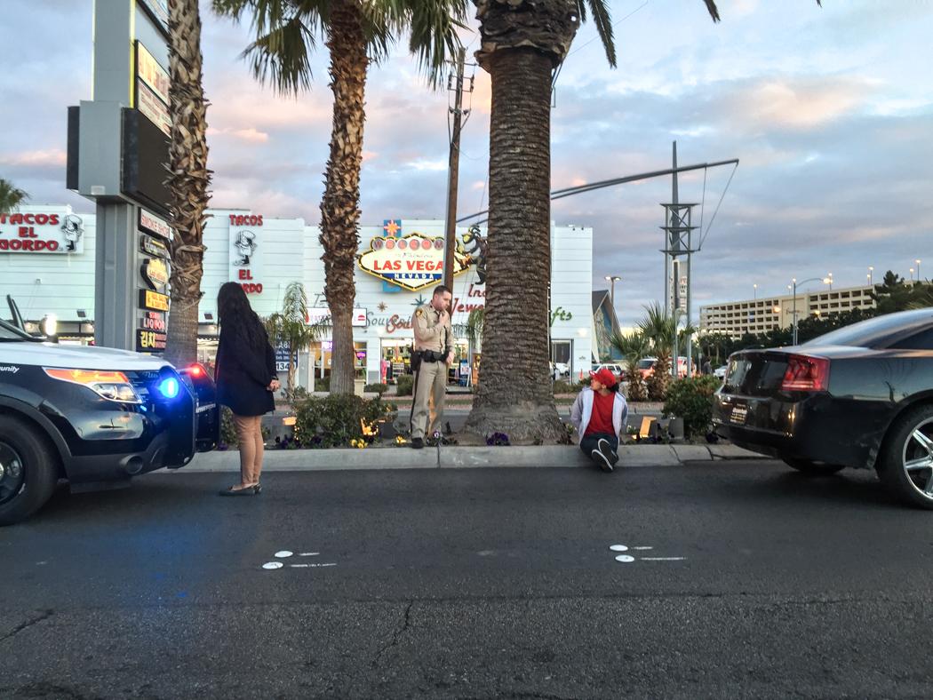 Hoppsan: en ung kvinna och en man har blivit gripna av polis på strippen och väntar med handklovar på, antar jag, förstärkning. Samtidigt blir de till en attraktion i sig.
