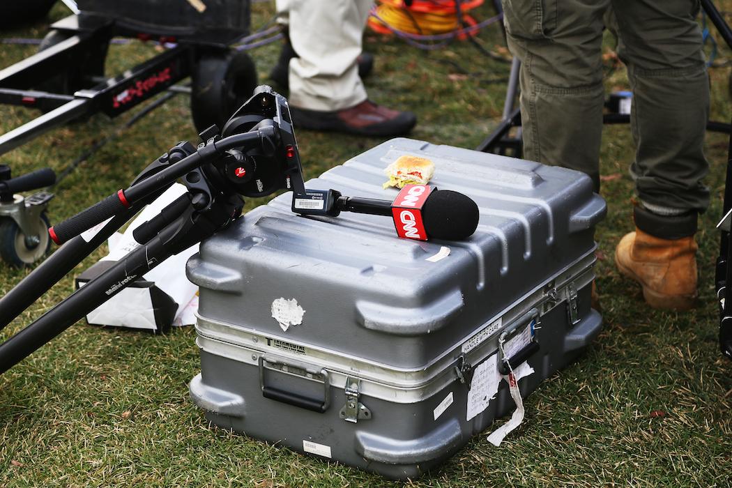 En medlem i CNN:s crew försöker hinna med att käka en macka under bevakningen av Donald Trumps jippo.