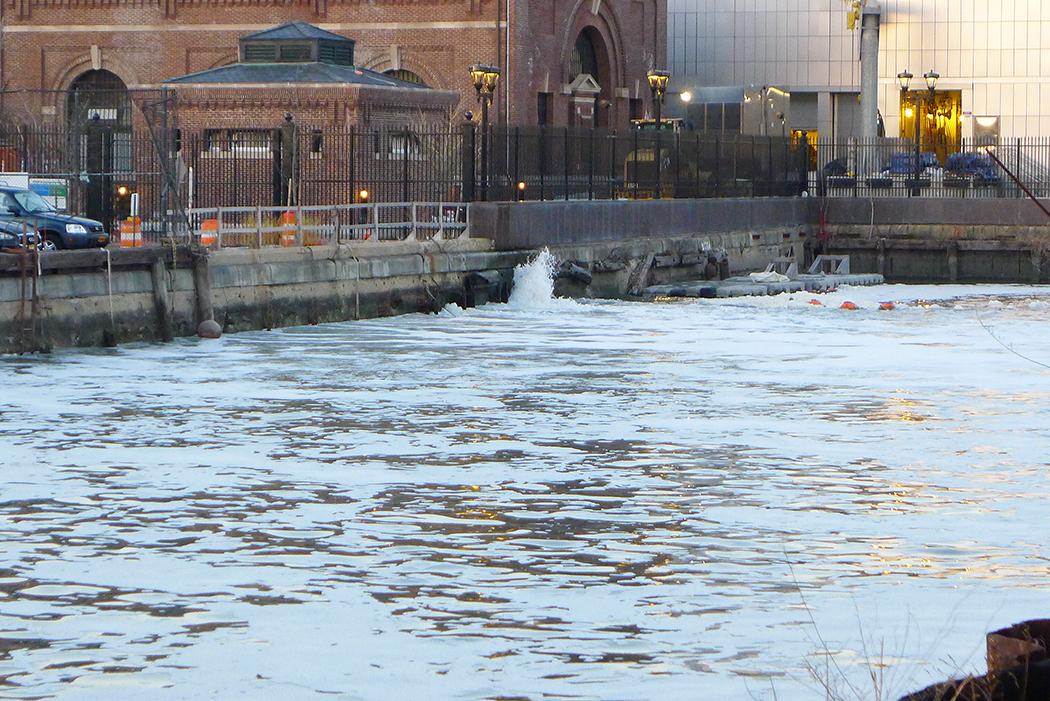 Norra änden på Gowanus Canal. Löddrigt vatten bubblar ut från under tegelbyggnaden till vänster. Foto: Erik Bergin