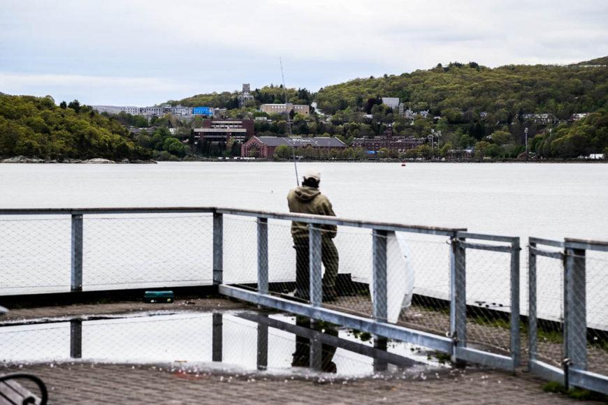 En snubbe står och fiskar i Cold Spring längs Hudson River, med officersskolan West Point tvärs över floden. Foto: Erik Bergin