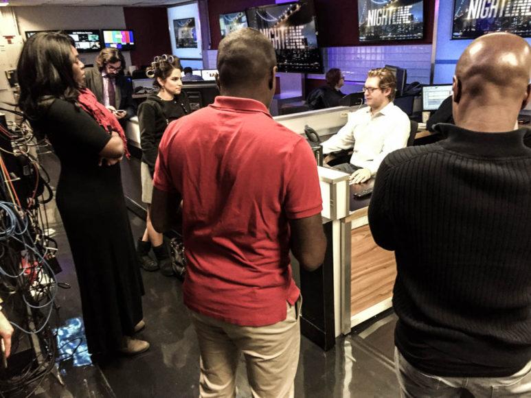 Nyhetsmöte nere i studion strax före sändning, strax efter midnatt. Killen i vit skjorta vänd hitåt är en av redaktörerna som väljer ut stories, röda tröjan och tjejen i papiljotter är programledarna. Foto: Erik Bergin